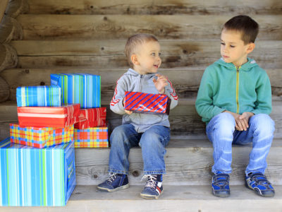 envious child. elder brother is jealous of a pile of gifts that