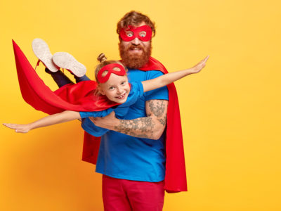 Small kid plays superhero, being on fathers hands, pretends flying, spreads arms sideways, wears red mask and cloak, enjoys spare time with dad, isolated on yellow wall. Daddy hero holds daughter